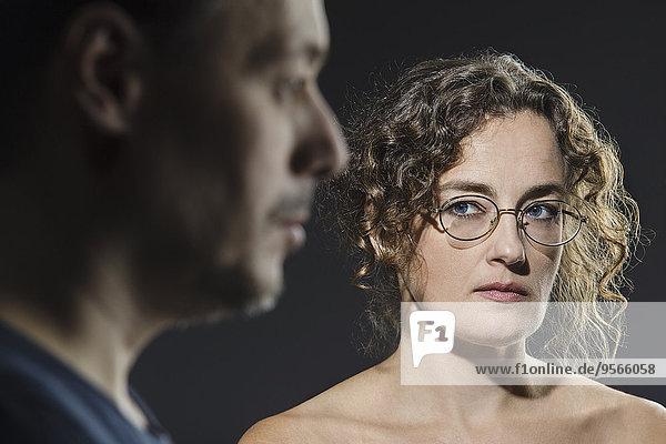 Wütende Frau  die den Mann im Vordergrund sieht.