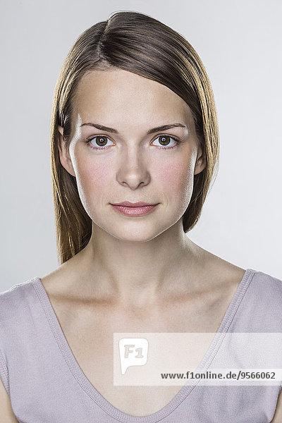 Nahaufnahme der schönen jungen Frau vor weißem Hintergrund