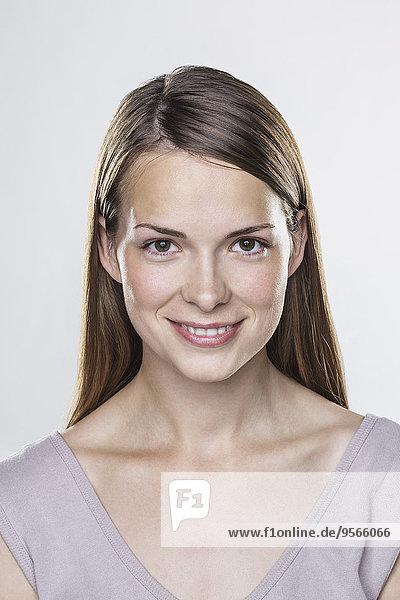 Nahaufnahme Porträt einer lächelnden jungen Frau vor weißem Hintergrund