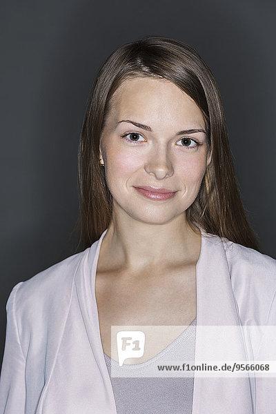 Porträt einer lächelnden jungen Frau vor schwarzem Hintergrund