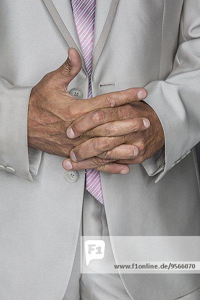 Mittelteil des Geschäftsmannes stehend mit umklammerten Händen