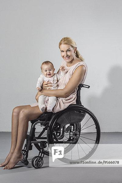 Portrait einer glücklichen Frau mit einem Mädchen im Rollstuhl vor grauem Hintergrund.