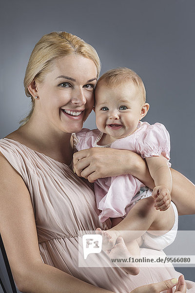 Porträt der glücklichen Mutter mit süßem Mädchen vor grauem Hintergrund