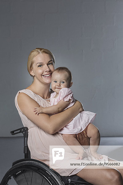 Porträt einer glücklichen Frau mit einem Mädchen im Rollstuhl an der grauen Wand