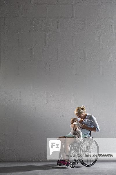 Volle Länge des stillenden Mädchens im Rollstuhl gegen graue Wand