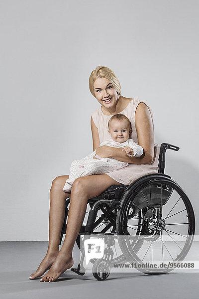 Ganzflächiges Porträt einer glücklichen Frau mit Tochter im Rollstuhl vor grauem Hintergrund