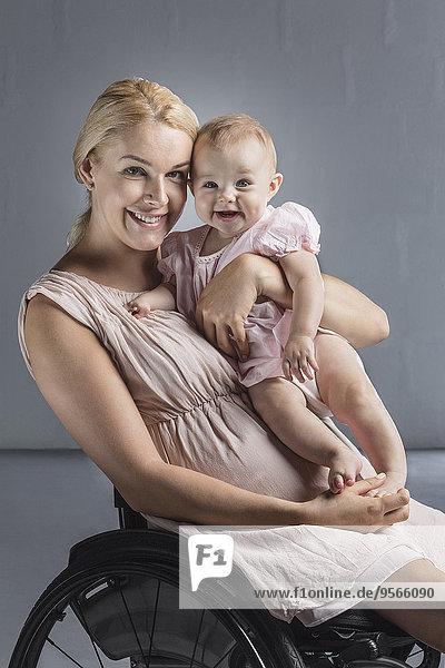 Porträt der glücklichen Mutter mit dem Mädchen im Rollstuhl gegen die graue Wand