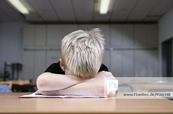 Ein kleiner Junge macht ein Nickerchen während des Studiums.