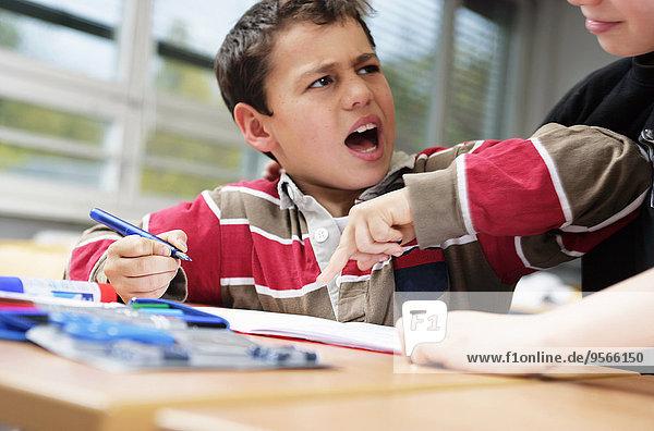 Ein kleiner Junge stört seinen Freund  während er seine Schularbeit macht.