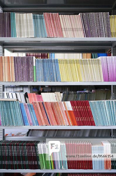 Viele farbenfrohe Bücher im Bücherregal angeordnet
