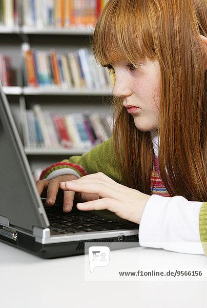 Ein Mädchen arbeitet an einem Laptop in einer Bibliothek.