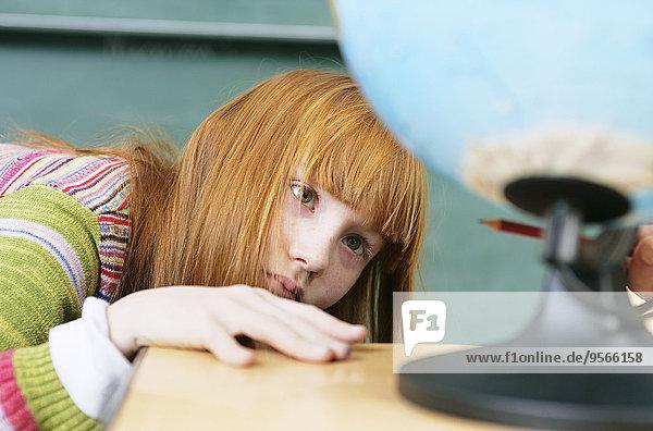 Ein Mädchen schaut auf den unteren Teil eines Globus.