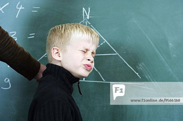 halten,Junge - Person,klein,grimassieren,Grimasse,Grimassen,schneiden,das Gesicht verziehen,Pullover,Lehrer