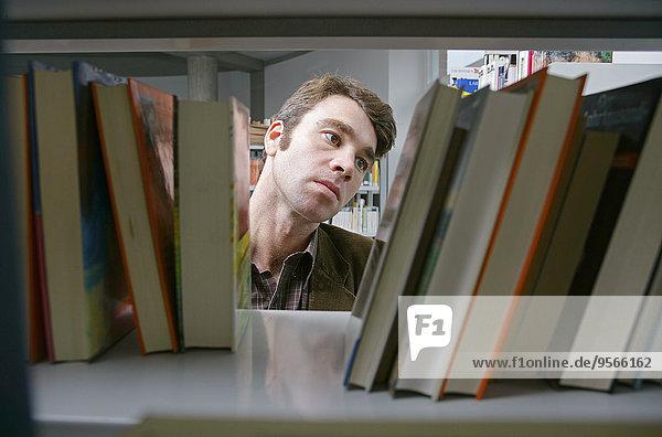 Ein Mann bewertet Bücher im Bücherregal.