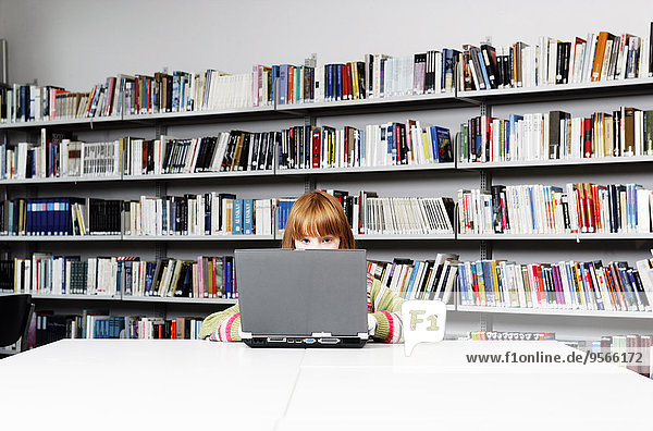 Ein Mädchen  das an einem Laptop in einer Bibliothek arbeitet.