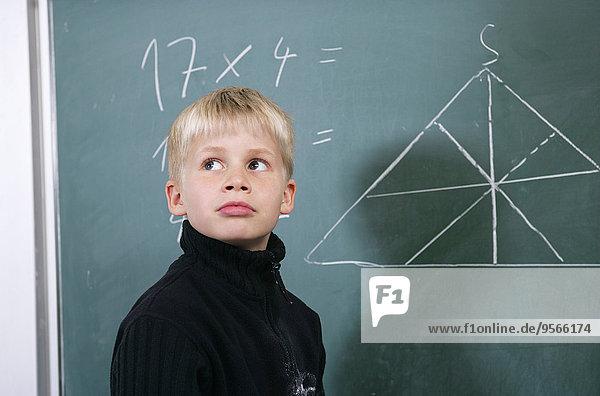 Ein Junge  der neben einer Tafel steht.