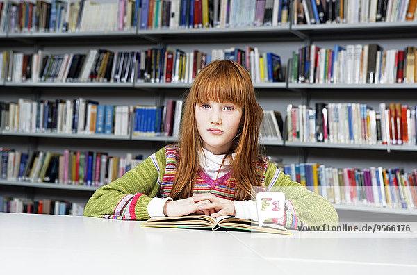 Ein Mädchen  das in einer Bibliothek sitzt.