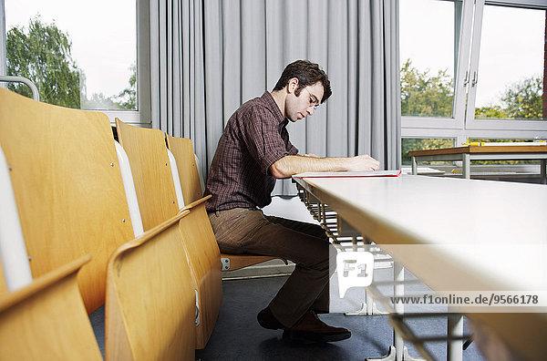 Seitenansicht eines im Hörsaal studierenden Mannes