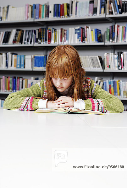 Ein Mädchen  das ein Buch in einer Bibliothek liest.
