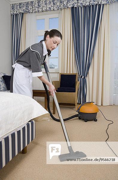 Uniformiertes Dienstmädchen mit Staubsauger im Hotelzimmer