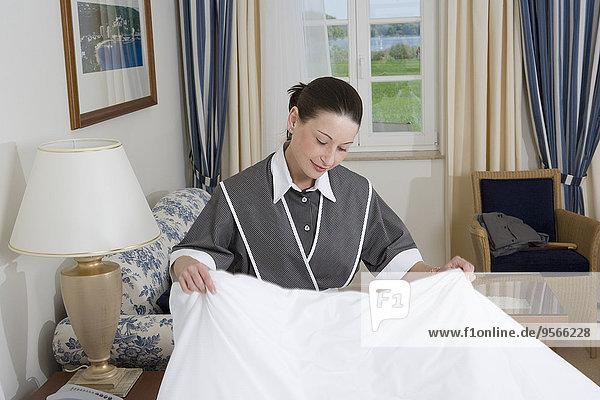 Uniformiertes Dienstmädchen macht Bett im Hotelzimmer