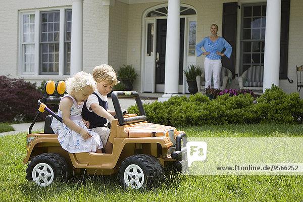 Ein Junge und ein Mädchen fahren in einem Spielzeug-Jeep