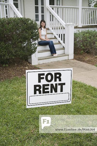 Eine junge Frau sitzt auf der Treppe eines Hauses hinter einem zu vermietenden Schild.