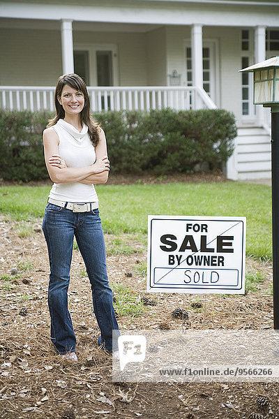 Eine junge Frau steht neben einem verkauften Schild vor einem Haus.