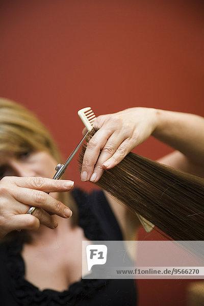 Ein Friseur  der einer Frau die Haare schneidet.
