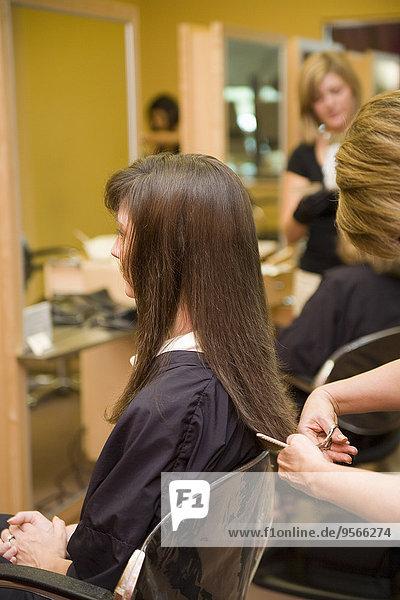 Eine junge Frau  die ihr Haar in einem Salon stylen lässt.