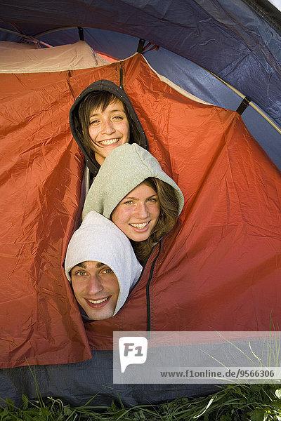 Drei Freunde drängten sich im Zelt.
