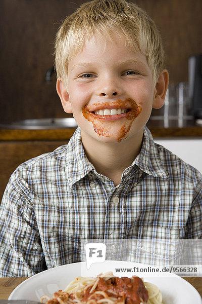 Junge mit Essen um den Mund herum lächelnd