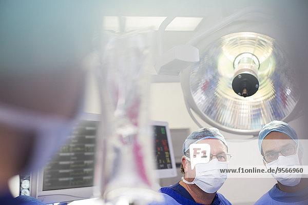 Zwei Chirurgen schauen während der Operation auf den Salinenbeutel