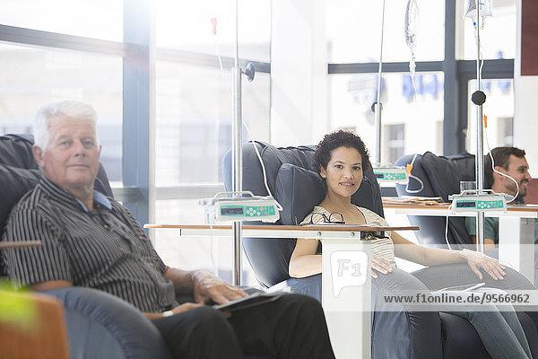Patienten  die in Sesseln sitzen und auf der Krankenstation behandelt werden