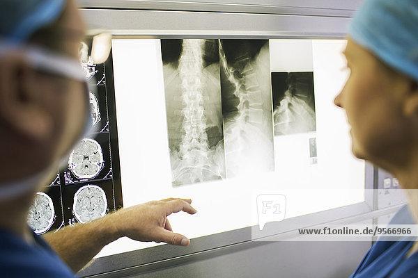 Zwei reife Ärzte diskutieren über Röntgen- und MRT-Scans von Patienten