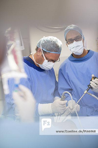 Reife Ärzte, die eine Operation durchführen und die Flüssigkeit im Kochsalzlösungsbeutel kontrollieren.