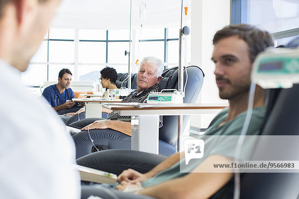 Ärzte im Gespräch mit medizinisch behandelten Patienten auf der Krankenstation
