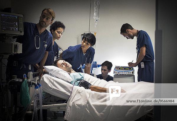 Gruppe von Ärzten  die den Patienten auf der Krankenstation betreuen
