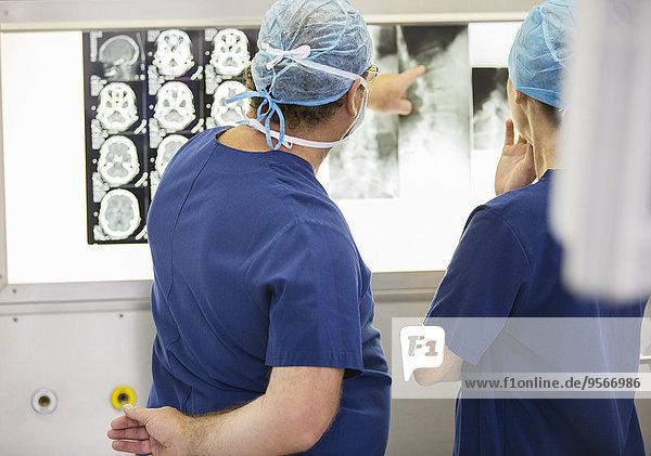 Zwei Ärzte besprechen Röntgen- und MRT-Aufnahmen des Patienten