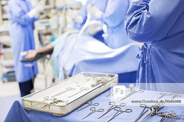 Krankenschwester steht mit chirurgischem Werkzeug im Operationssaal bereit