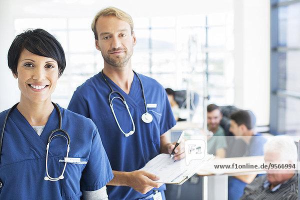 Porträt von Ärzten mit Patienten  die im Hintergrund behandelt werden