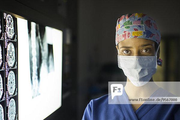 Portrait einer jungen Ärztin in der Nähe des Bildschirms mit MRT-Aufnahme