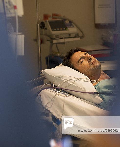 Männlicher Patient schläft im Krankenhausbett