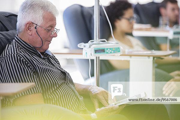 Seniorenpatientin, die im Sitzen und Lesen auf der Krankenstation behandelt wird.