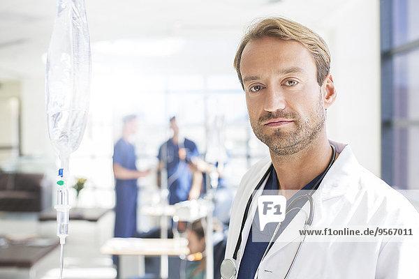 Porträt eines Arztes mittlerer Größe mit Kollegen im Hintergrund, stehend auf der Krankenstation