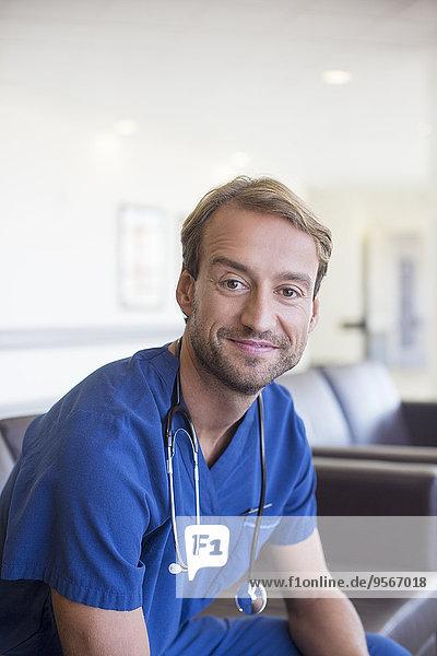 Porträt eines Arztes mittlerer Größe lächelnd und sitzend auf einem Ledersofa im Flur des Krankenhauses