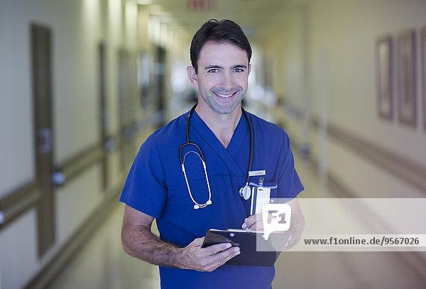 Porträt eines männlichen Arztes mit Klemmbrett im Krankenhausflur