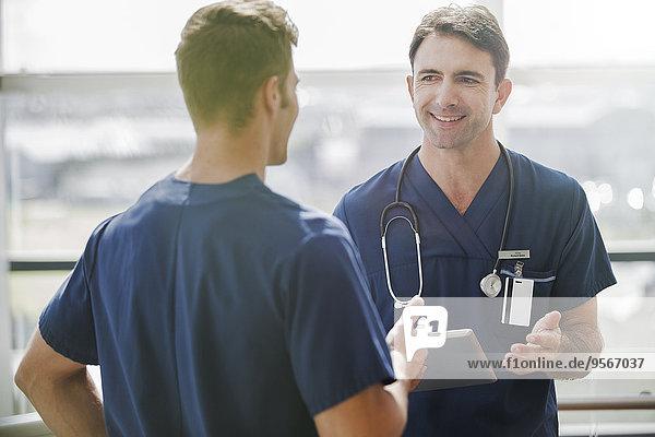 Zwei Ärzte im Gespräch, einer hält Tabletten-PC