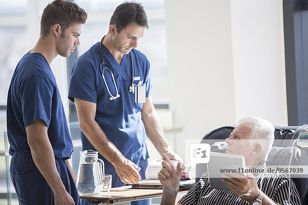 Patient mit Tablet-PC und Gespräch mit Ärzten im Krankenhaus