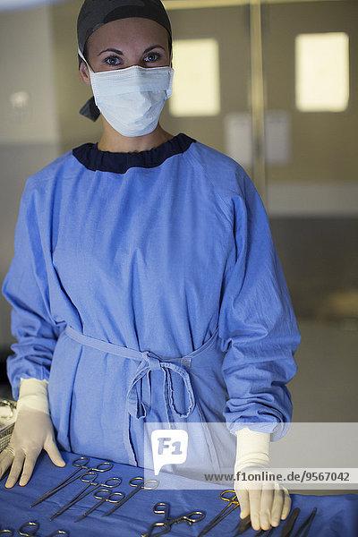 Portrait eines maskierten Chirurgen mit chirurgischem Instrumentarium im Operationssaal